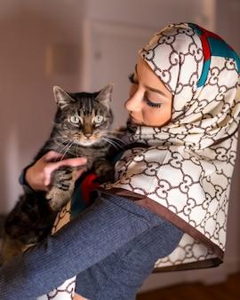 Portret van een witte gesluierde jonge vrouw met een mooie kat thuis