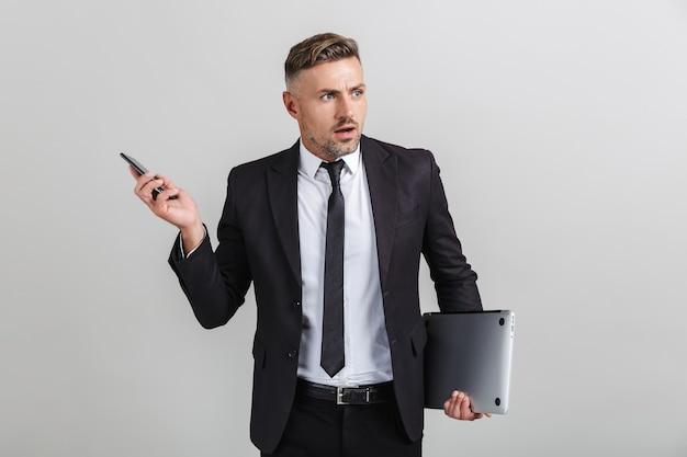 Portret van een woedende volwassen zakenman in een kantoorpak met smartphone en laptop terwijl hij geïsoleerd staat