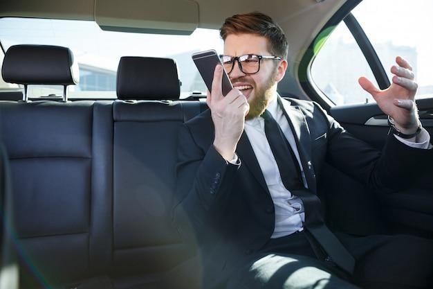 Portret van een woedende zakenman schreeuwen tegen mobiele telefoon