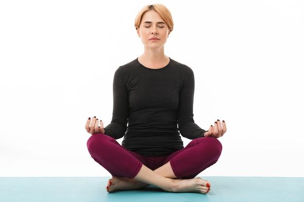 Portret van een yogavrouw die in lotusbloempositie mediteert
