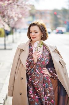Portret van een zachte vrouw tegen de achtergrond van sakura bloemen. loop in de bloeiende sakura-tuin. jonge stijlvolle vrouw die in het sakura-park staat en geniet van schoonheid