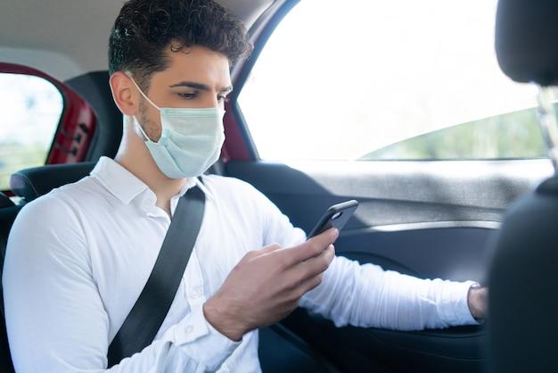 Portret van een zakenman die een gezichtsmasker draagt en zijn mobiele telefoon gebruikt op weg naar zijn werk in een auto