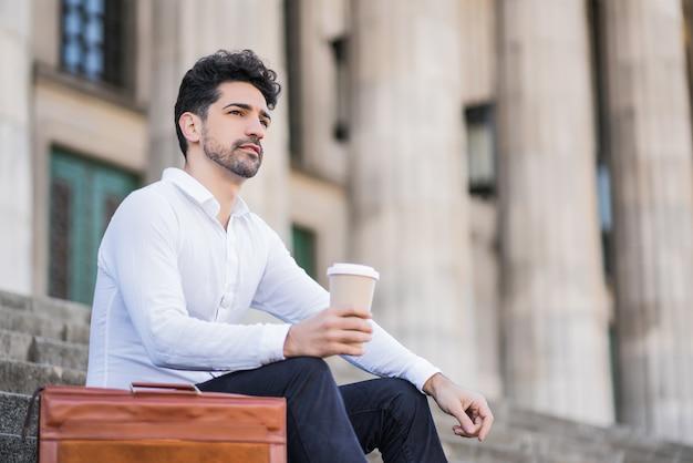 Portret van een zakenman die een kopje koffie drinkt tijdens een pauze van het werk zittend op de trap buiten