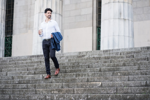 Portret van een zakenman die een kopje koffie houdt op weg naar buiten te werken. bedrijfsconcept.