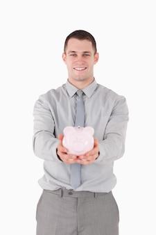 Portret van een zakenman die een spaarvarken houdt
