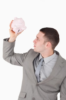 Portret van een zakenman die in een spaarvarken kijkt