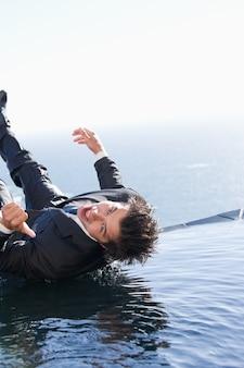 Portret van een zakenman die in water valt