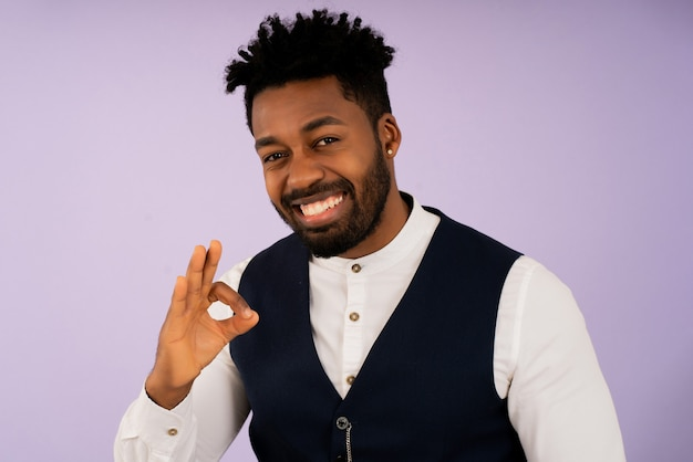 Portret van een zakenman die lacht en een goed gebaar maakt met zijn hand terwijl hij tegen een geïsoleerde achtergrond staat. bedrijfsconcept.