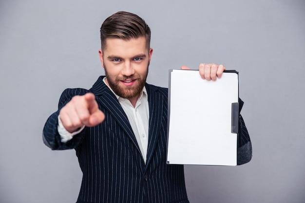 Portret van een zakenman die leeg klembord toont en vinger toont op camera over grijze muur