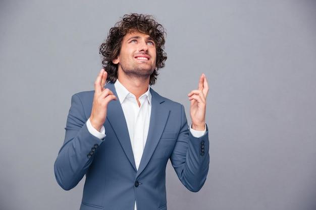 Portret van een zakenman die met gekruiste vingers over grijze muur bidt en omhoog kijkt