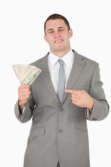 Portret van een zakenman die op een pakje contant geld richt