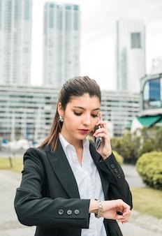 Portret van een zakenman die tijd controleert op haar polshorloge