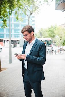 Portret van een zakenman die zich op straat bevindt die mobiele telefoon met behulp van