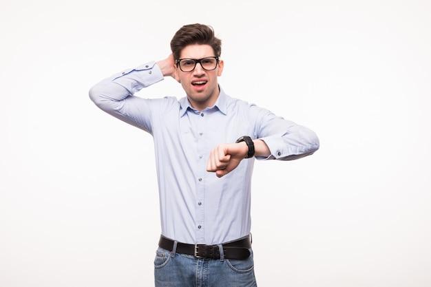 Portret van een zakenman die zijn polshorloge bekijkt dat over witte ruimte wordt geïsoleerd