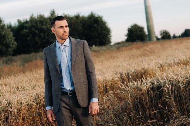 Portret van een zakenman in een grijs pak in een tarweveld. een man in de natuur in een jasje en stropdas.