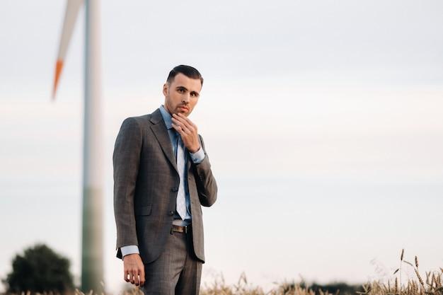 Portret van een zakenman in een grijs pak op een tarweveld tegen de achtergrond van een windmolen en de avondlucht.