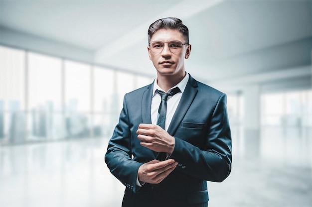 Portret van een zakenman in een pak. hij staat in het kantoor van een wolkenkrabber. bedrijfsconcept.