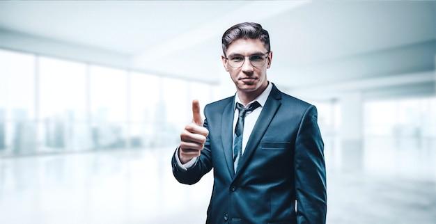 Portret van een zakenman in een pak. hij staat in het kantoor van een wolkenkrabber en steekt zijn duim op. bedrijfsconcept.