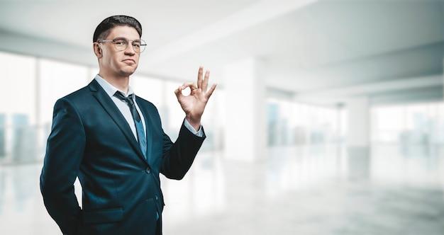 Portret van een zakenman in een pak. hij staat in het kantoor van een wolkenkrabber. ok teken. bedrijfsconcept.