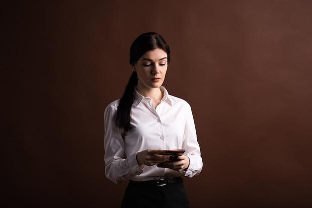 Portret van een zakenvrouw die haar smartphone in de studio op een bruine achtergrond gebruikt