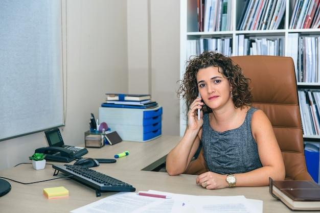 Portret van een zakenvrouw die kijkt terwijl ze praat met een smartphone die op kantoor zit