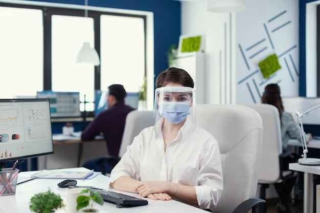 Portret van een zakenvrouw die naar een camera kijkt die op een stoel zit en een gezichtsmasker draagt tegen covid19. business team dat werkt in een financieel bedrijf met respect voor sociale afstand tijdens wereldwijde pandemie.