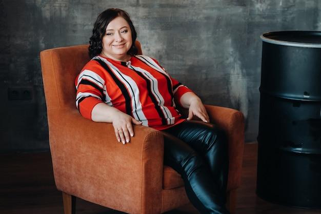 Portret van een zakenvrouw in een gestreepte jas, zittend op een bank in het interieur.