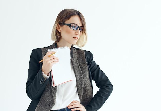 Portret van een zakenvrouw in een pak met documenten in handen op een lichte achtergrond