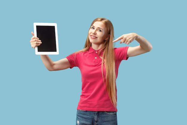 Portret van een zeker toevallig meisje dat het lege scherm van laptop toont dat over blauwe muur wordt geïsoleerd