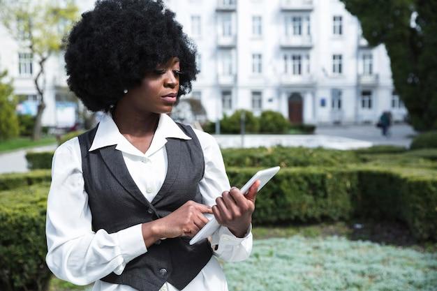 Portret van een zekere afrikaanse jonge onderneemster die digitale tablet bekijken