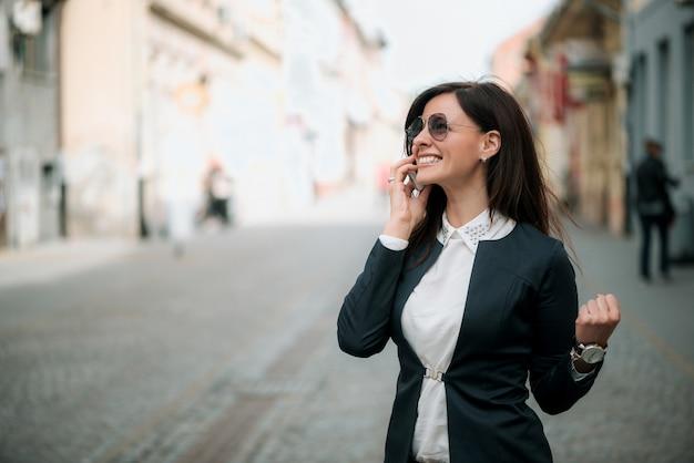 Portret van een zekere bedrijfsvrouw die op telefoon spreekt
