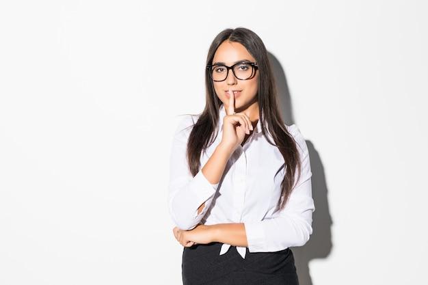 Portret van een zekere jonge bedrijfsvrouw die stiltegebaar tonen en op wit wordt geïsoleerd