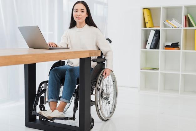 Portret van een zekere jonge onderneemsterzitting op rolstoel die laptop in het bureau met behulp van