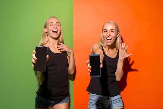 Portret van een zekere toevallige meisjes die lege het scherm mobiele telefoon tonen die over kleurrijke achtergrond wordt geïsoleerd