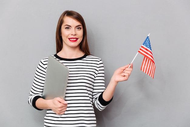 Portret van een zekere vrouw die amerikaanse vlag houdt