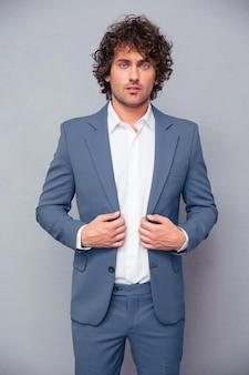 Portret van een zekere zakenman die zich over grijze muur bevindt en voorzijde bekijkt