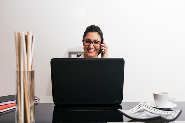 Portret van een zelfstandige vrouw met een bril praten aan de telefoon tijdens het werken vanuit huis in haar geïmproviseerde kantoor
