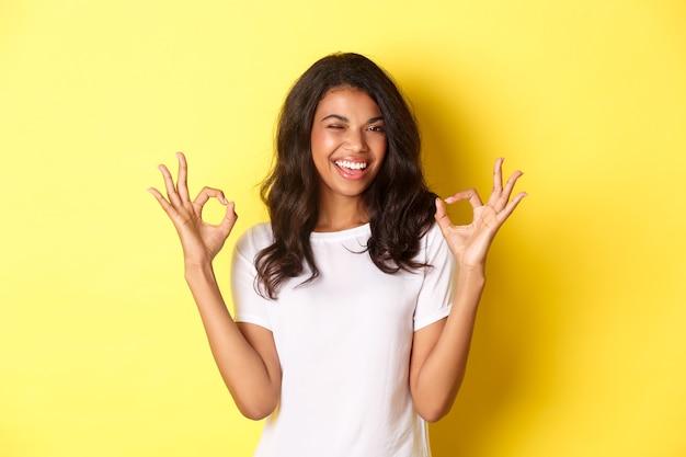 Portret van een zelfverzekerd, aantrekkelijk afro-amerikaans meisje, dat goede tekens toont en knipoogt, kwaliteit garandeert, iets goeds goedkeurt en ermee instemt, staande op een gele achtergrond.
