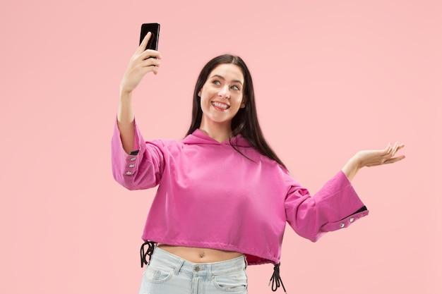 Portret van een zelfverzekerd, gelukkig lachend casual meisje dat een selfie-foto maakt via een mobiele telefoon die over een roze muur wordt geïsoleerd.