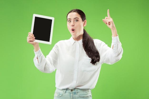 Portret van een zelfverzekerd toevallig meisje dat het lege scherm van laptop toont