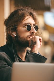 Portret van een zelfverzekerde bebaarde man in oortelefoons