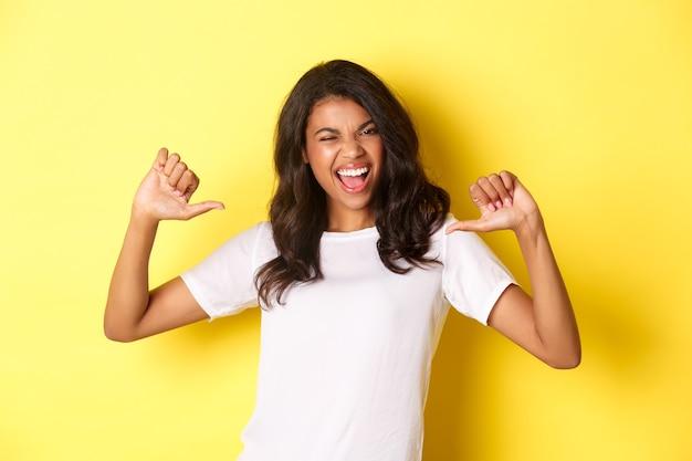 Portret van een zelfverzekerde en gelukkige afro-amerikaanse vrouw die met de vinger naar zichzelf wijst en trots lacht