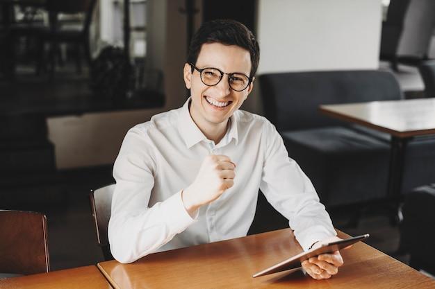 Portret van een zelfverzekerde gelukkig zakenman gekleed in een wit overhemd zit aan zijn bureau in zijn restaurant met een tablet in zijn hand camera kijken lachen.