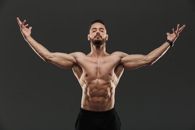 Portret van een zelfverzekerde gespierde bodyuilder poseren