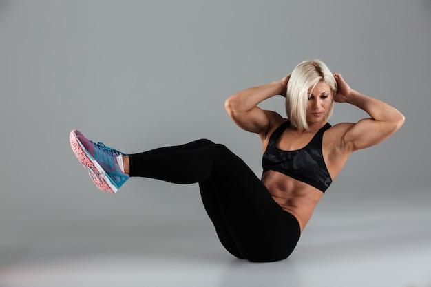 Portret van een zelfverzekerde gespierde volwassen sportvrouw