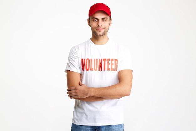 Portret van een zelfverzekerde glimlachende mens die vrijwilligerst-shirt draagt