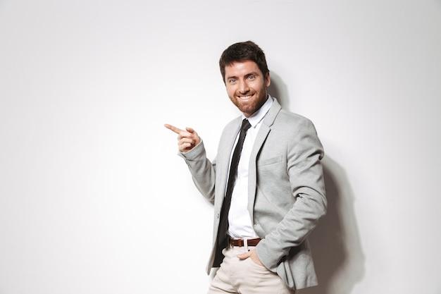 Portret van een zelfverzekerde jonge man gekleed in pak staande geïsoleerd, wijzend op kopie ruimte