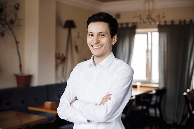 Portret van een zelfverzekerde jonge manager die camera bekijkt die met gesloten hand glimlacht, gekleed in het wit.