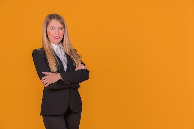 Portret van een zelfverzekerde jonge vrouw met haar arm gekruist staande tegen een oranje achtergrond