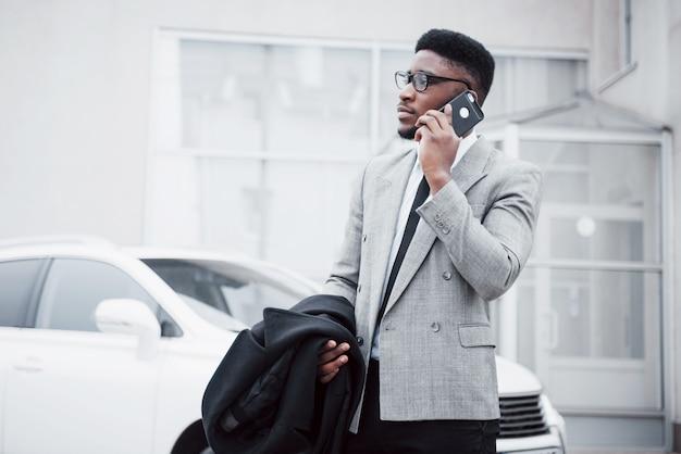 Portret van een zelfverzekerde jonge zakenman die in de stad loopt die op celtelefoon spreekt